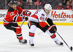 Dec 18, 2013; Newark, NJ, USA;  New Jersey Devils right wing Damien Brunner (12) chases Ottawa Senators defenseman Erik Karlsson (65) during the second period at the Prudential Center.