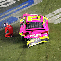 NASCAR Sprint Cup drivers AJ Allmendiner (51) falls to the ground after a wreck during the NASCAR Coke Zero 400 Sprint series auto race at the Daytona International Speedway on Saturday, July 6, 2013 in Daytona Beach, Florida.  (AP Photo/Alex Menendez)