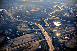 CANADA ALBERTA FORT MCMURRAY 23JUL09 - View of Suncor Millennium tailings pond and tarsands mining operations north of Fort McMurray, northern Alberta, Canada...The tar sand deposits lie under 141,000 square kilometres of sparsely populated boreal forest and muskeg and contain about 1.7 trillion barrels of bitumen in-place, comparable in magnitude to the world's total proven reserves of conventional petroleum. Current projections state that production will  grow from 1.2 million barrels per day (190,000 m³/d) in 2008 to 3.3 million barrels per day (520,000 m³/d) in 2020 which would place Canada among the four or five largest oil-producing countries in the world...The industry has brought wealth and an economic boom to the region but also created an environmental disaster downstream from the Athabasca river, polluting the lakes where water and fish are contaminated. The native Indian tribes of the Mikisew, Cree, Dene and other smaller First Nations are seeing their natural habitat destroyed and are largely powerless to stop or slow down the rapid expansion of the oil sands development, Canada's number one economic driver...jre/Photo by Jiri Rezac / GREENPEACE..© Jiri Rezac 2009