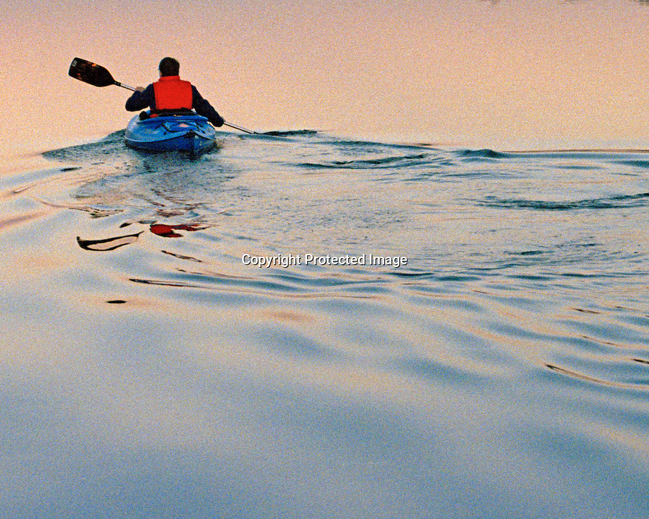 "Lone kayaker at sunset paddling away leaving silver wake behind on lake near Georgetown, Texas. NOTE: Click ""Shopping Cart"" icon for available sizes and prices. If a ""Purchase this image"" screen opens, click arrow on it. Doing so does not constitute making a purchase. To purchase, additional steps are required."