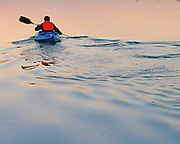 """Lone kayaker at sunset paddling away leaving silver wake behind on lake near Georgetown, Texas. NOTE: Click """"Shopping Cart"""" icon for available sizes and prices. If a """"Purchase this image"""" screen opens, click arrow on it. Doing so does not constitute making a purchase. To purchase, additional steps are required."""