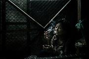 Woman smoking at Saphan Pla fish market in Bangkok, some Burmese migrant are working illegally.           Femme fumant au marché aux poissons de Saphan Pla à Bangkok, certaines migrantes birmanes travaillent illégalement.