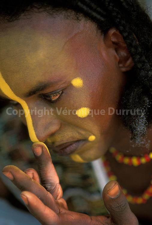 Jeune homme se préparant pour la cérémonie..La fête annuelle traditionnelle du Geerewol est pratiquée uniquement par les hommes qui se présentent en ligne, maquillés, parés de bijoux et de leurs plus beaux atouts. Ils chantent et dansent lentement pour offrir aux femmes leurs sourires crispés et leurs yeux écarquillés afin de mettre en avant l'esthétique de leur visages. Les jeunes filles bororo se mêlent ensuite aux danseurs et choisissent les plus beaux...Jeune homme se préparant pour la cérémonie..La fête annuelle traditionnelle du Geerewol est pratiquée uniquement par les hommes qui se présentent en ligne, maquillés, parés de bijoux et de leurs plus beaux atouts. Ils chantent et dansent lentement pour offrir aux femmes leurs sourires crispés et leurs yeux écarquillés afin de mettre en avant l'esthétique de leur visages. Les jeunes filles bororo se mêlent ensuite aux danseurs et choisissent les plus beaux.
