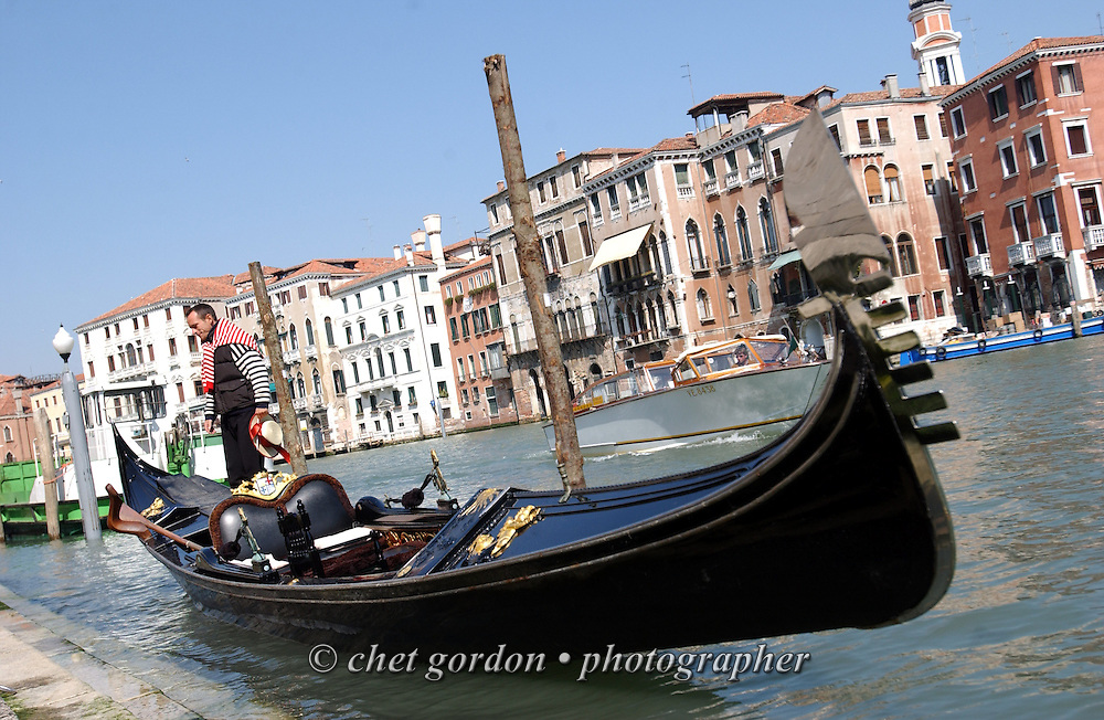 Gondolier awaits a fare along the Grand Canal near the marketplace in Venice, Italy. April 2002.