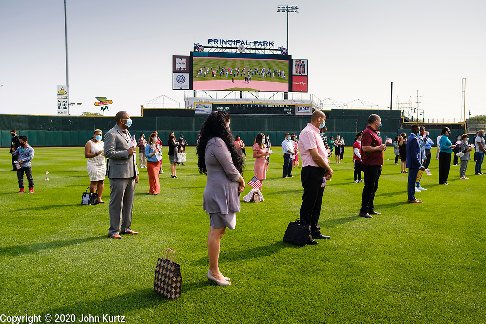 17 SEPTEMBER 2020 - DES MOINES, IOWA: New citizens line up in the outfield during a naturalization ceremony at Principal Park, a minor league baseball stadium in downtown Des Moines. About 75 people from 32 countries were naturalized as US citizens Thursday. It was the last citizenship ceremony in Des Moines before citizenship fees dramatically increase. Starting Oct. 2, the fee to apply for U.S. citizenship will increase from $640 to $1,160 if filed online, or $ 1,170 in paper filing, a more than 80% increase in cost. Advocates for immigration are afraid the new fees will be too expensive for many immigrants and say it's an effort by the Trump Administration to limit the number of new citizens welcomed into the United States. Because of the COVID-19 pandemic, there has been dramatic slow down in the number of naturalization ceremonies this year.    PHOTO BY JACK KURTZ