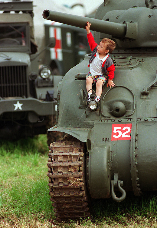 Nicolas Lecointe, a French boy, sits on a Sherman tank while visiting an encampment of vintage vehicles along the Normandy Coast . The 1944-94 Overlord Jubilee rally was part of the 50th Anniversary of the D-Day landings.
