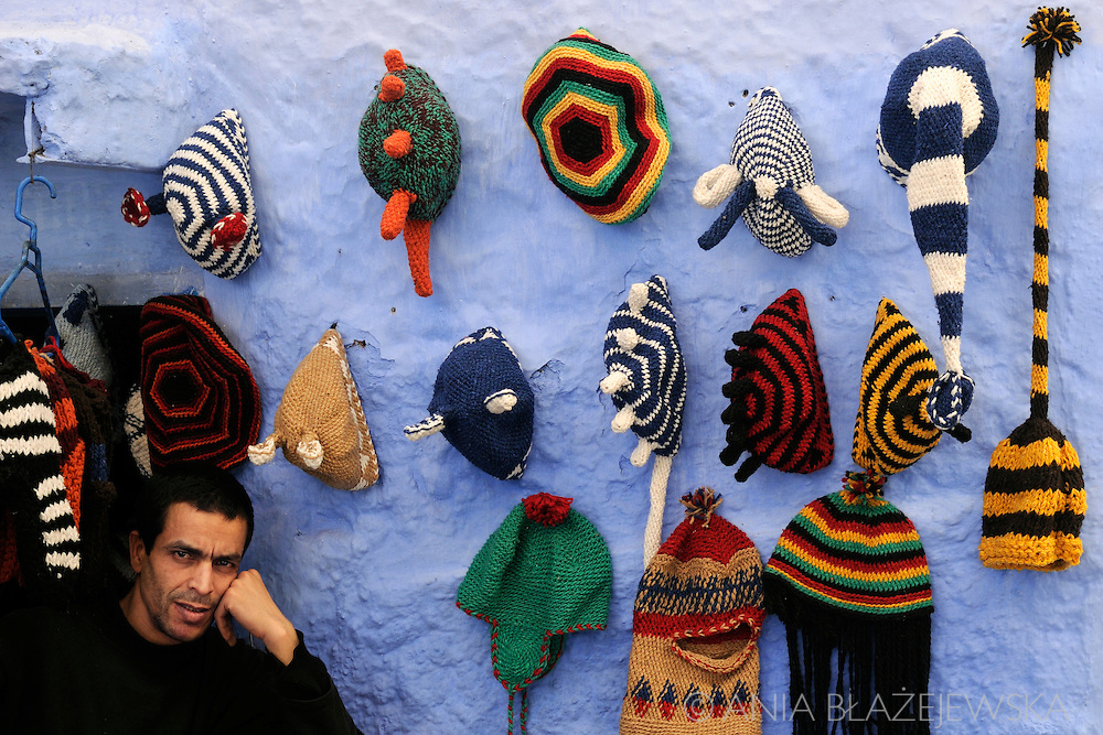 Morocco, Chefchaouen. Man selling colorful caps in the blue medina of Chefchaouen.