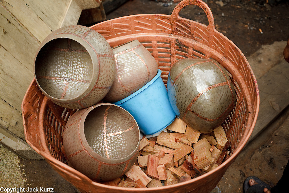 """Mar. 21, 2009 -- BANGKOK, THAILAND:  Monk's Bowls wait to be finished in a workshop in the Monk's Bowl Village. The Monk's Bowl Village on Soi Ban Baat in Bangkok is the only surviving one of what were originally three artisan's communities established by Thai King Rama I for the purpose of handcrafting """"baat"""" the ceremonial bowls used by monks as they collect their morning alms. Most monks now use cheaper factory made bowls and the old tradition is dying out. Only six or seven families on Soi Ban Baat still make the bowls by hand. Most of the bowls are now sold to tourists who find their way to hidden alleys in old Bangkok. The small family workshops are only a part of the """"Monk's Bowl Village."""" It is also a thriving residential community of narrow alleyways and sidewalks.     Photo by Jack Kurtz"""