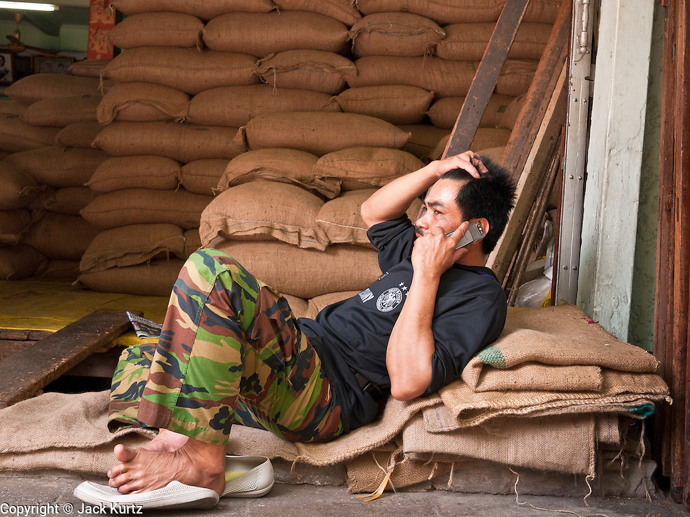 09 JULY 2011 - BANGKOK, THAILAND: A man talks on a mobile phone at a peanut warehouse in the Chinatown section of Bangkok, Thailand. Chinatown is the entrepreneurial hub of Bangkok, with thousands of family owned businesses selling wholesale merchandise in everything from food like rice, peanuts and meats, to dry goods like toys and shoes.  PHOTO BY JACK KURTZ