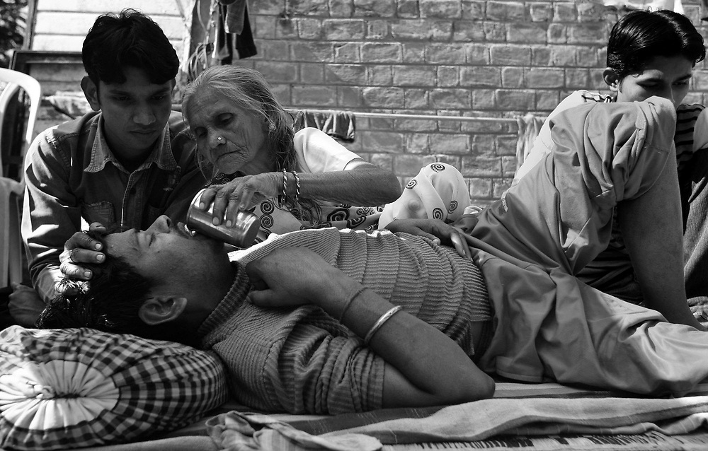 "Prembai, 70, pours milk down her 40-year-old son, Hemant's throat. The Bhopal Memorial Hospital and Research Centre, built specifically for gas victims, say they can only give him 1 or 2 dialysis and then he will need to go private, which they cannot afford, and Prembai wonders if it's better for him to have a little dialysis and stop or to have no dialysis at all. ""What we saw, what we went through that night was horrific, too much suffering. But now, many years later, and the suffering hasn't stopped."""
