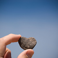 A heart shaped rock held in two fingers against a blue sky as if being inspected in better light.