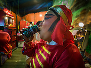 04 FEBRUARY 2017 - BANGKOK, THAILAND: A Chinese opera performer drinks a can of iced coffee during an opera performance for the Lunar New Year at the Phek Leng Keng Shrine in the Khlong Toey section of Bangkok. Many Chinese shrines and temples host Chinese operas during the Lunar New Year. Lunar New Year was January 28 this year and opera troupes are finishing their holiday engagements at the local temples.     PHOTO BY JACK KURTZ