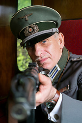 A Reenactor portraying a German Army (heer) Medical Captain (Hauptmann) aims his MP38 on the East Lancashire Railway 1940's Weekend. He is wearing an officer's Schirmmütze<br />