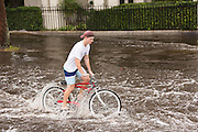 A bicyclist makes way through floodwater along the Battery in the historic district as Hurricane Joaquin brings heavy rain, flooding and strong winds as it passes offshore October 4, 2015 in Charleston, South Carolina.