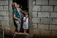 Remy Fernandez, 84 years old, holds her grandchild in the front door of her simple cinder block house built beside a massive mountain of garbage in Payatas, Metro Manila.<br /> <br /> She is raising seven grandchildren, because her son, Constantino de Juan, a methampetamine user, was killed by masked men and the mother is in prison due to a drug arrest.  The masked assassins passed through this front door and shot him while on his knees in front of a sofa which still bears the hole it after passing through his body.  She is holding Baby RJ who was born in prison.  Metro Manila, Philippines