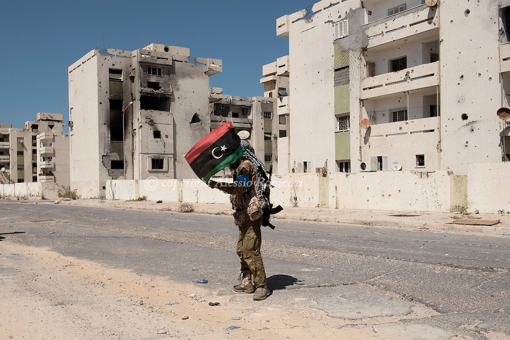 Libya, Sirte: a fighter sympathising with Libya's Government of National Accord's (GNA) waves the Libyan flag in district 2 in Sirte right after has been freed from ISIS fighters. Alessio Romenzi