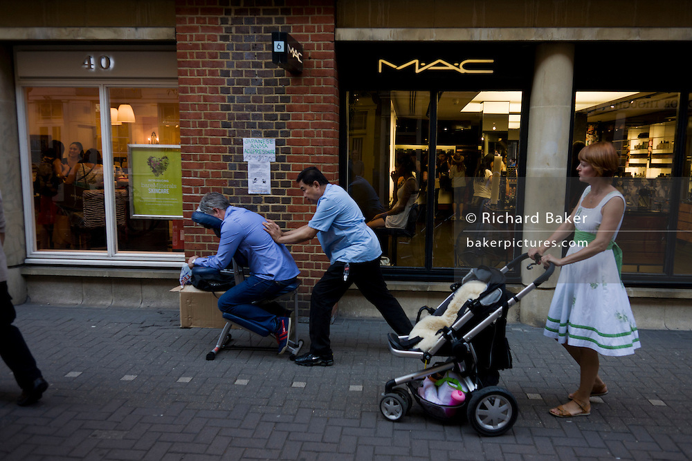 A masseuse pushes the sore back of a street patient during the demonstration of an Anma acupressure treatment in a central London street. Anma is Japanese for 'press and rub'. Matching the stance of the practitioner wearing a blue tunic who puts his weight forward into the pressure point of the lumbar area, a young mother holds on to the pushchair of her young child. There are many different methods in Anma, including massage, acupressure, stretching But it is important to note that there are many different versions of anma. Many massage therapists in the west have adapted this old technique to work with their more modern methods. Most common is the stretching, pulling, and pulling of affected areas. This is done to try and achieve the release of muscle tension that in return will help to encourage the proper blood flow and lymph flow.