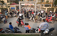 Parents wait for their kids to pick them up after school. They park their motorbikes in front of the gate. Hanoi, Vietnam, Asia.