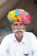 Senior Indian man from Rajasthan in India. He is photographed here at Pushkar Fair and has a brightly coloured turban, a luxuriant long moustache and gold earrings.
