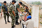 "27 FEBRUARY 2008 -- MAE SOT, TAK, THAILAND: Thai soldiers on the Thai side of the border talk to Burmese cigarette smugglers on the Burmese side of the border along the Thai - Myanmar (Burma) border in Mae Sot, Thailand. Thai authority ends at the metal railing separating the men and Burmese smugglers line up along the rail to sell cigarettes and liquor to people on the Thai side of the rail. There are millions of Burmese migrant workers and refugees living in Thailand. Many live in refugee camps along the Thai-Burma (Myanmar) border, but most live in Thailand as illegal immigrants. They don't have papers and can not live, work or travel in Thailand but they do so ""under the radar"" by either avoiding Thai officials or paying bribes to stay in the country. Most have fled political persecution in Burma but many are simply in search of a better life and greater economic opportunity.  Photo by Jack Kurtz"