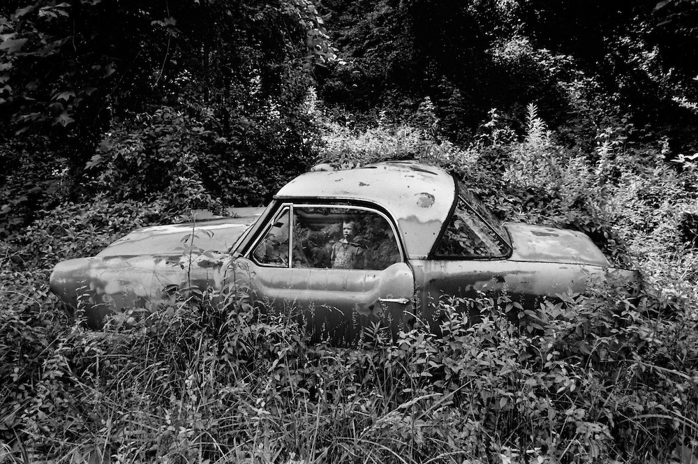 Abandoned Nash metropolitan in elkhorn, WV with a little boys reflection in the window.