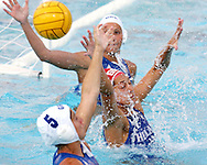 Greek goal keeper (red) and teammate Kyriaki Liosi (5) defend a shot on goal by Italy during the gold medal match between Greece and Italy in the Women's Water Polo final at the Olympic Aquatic Centre in Athens Thursday 26 August 2004. (Photo by Patrick B. Kraemer / MAGICPBK)