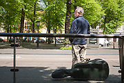 Een man wacht met zijn instrument bij de bushalte in Utrecht.<br />