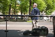 Een man wacht met zijn instrument bij de bushalte in Utrecht.<br /> <br /> A man is waiting with his instrument at a bus stop in Utrecht.