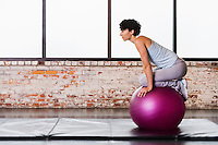 A young woman balancing atop an exercise ball while kneeling on it.