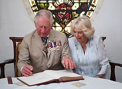 The Prince of Wales and the Duchess of Cornwall sign the visitor's book during their meeting with the Governor-General of Barbados, Her Excellency Dame Sandra Mason at Government House, Bridgetown, Barbados, as they continue their tour of the Caribbean.