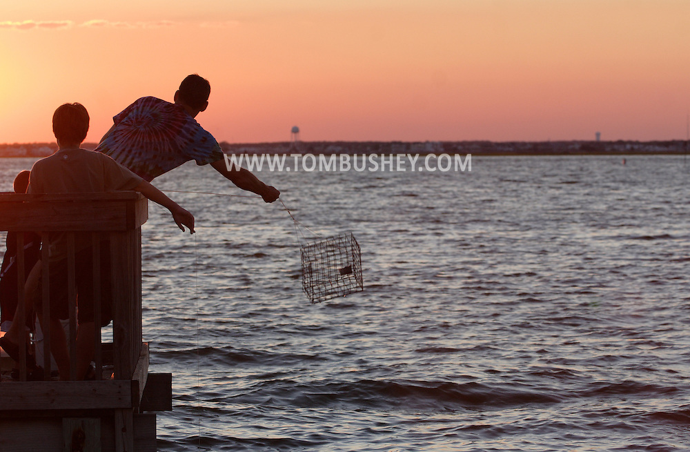 Beach Haven, New Jersey - A man throws a crab trap into Little Egg Harbor Bay off Long Beach Island on July 12, 2007. He was trying to catch blue claw crabs. MR