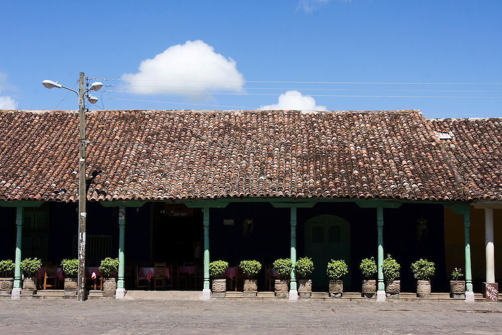 A veranda lined with potted ficus trees and the facade of a colonial building on the main square in Granada, Nicaragua.