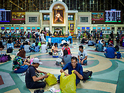 11 APRIL 2018 - BANGKOK, THAILAND:  People sit in the waiting area while they wait for their trains at Hua Lamphong train station in Bangkok on the first day of the Songkran travel period. Songkran is the traditional Thai New Year and is one of the busiest travel periods of the year as Thais leave the capital and go back to their home provinces or resorts in tourist areas. Trains and busses are typically jammed the day before the three day Songkran holiday starts. The government has extended the official holiday period through Monday, 16 April because one day of the Songkran holiday fell on the weekend, giving many workers a five day holiday.    PHOTO BY JACK KURTZ