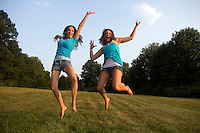 Two young women jump for joy in a rural meadow