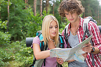 Young hiking couple reading map together in forest
