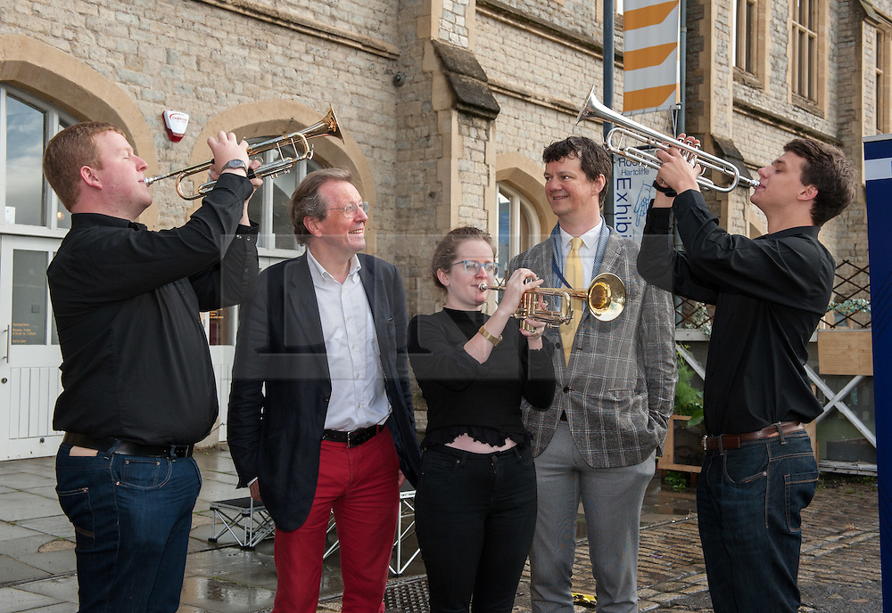 "© Licensed to London News Pictures. 27/07/2015. Bristol, UK.  ""Fanfare for Bristol"", titled ""At the Top of the Tide"", composed by David Mitcham, commissioned by Bristol Proms 2015.  Picture shows trumpeters l-r: Chris Hart, Helen Whitemore, Gideon Brooks, performing live for the Mayor of Bristol, George Ferguson (in red trousers) and Artistic Director of the Bristol Old Vic, Tom Morris for the first time at Bristol's famous Temple Mead train station, heralding the opening of the Bristol Proms 2015.  David Mitcham's  ""At the Top of the Tide"" was inspired by 'Bristol's inextricable links to the sea'.  The first performance by Arc Brass took place outside the Engine Shed, and throughout the day, performances took place at the Watershed, Pero's Bridge, the Wills Memorial Bell Tower and finally at Bristol Old Vic itself. David Mitcham, who has worked extensively for the BBC Natural History Unit based in Bristol said: ""I am thrilled that my Fanfare ""At the Top of the Tide"" has been chosen for the city of Bristol and to open Bristol Proms 2015. I hope the Fanfare represents the rich diversity of Bristol, its maritime and industrial heritage as well as being a celebration of the spirit of the city and the energy it will carry into the future.""  Bristol Proms 2015 runs from today, 27th July to 1st August and features some of the world's finest musicians including Alison Balsom, Miloš Karadaglić, Pumeza Matshikiza and Daniel Hope.  Photo credit : Simon Chapman/LNP"