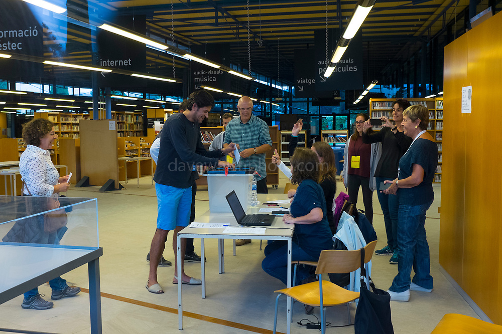 The first vote is cast at Biblioteca Central Gabriel Ferrater, Sant Cugat del Valles, just outside Barcelona, Catalonia, so that they can vote in the Catalan Independence Referendum. People had spend the night guarding the voting stations so that they were not seized by police. <br /> <br /> October 1st 2017, Catalans voted in a binding referendum to decide whether the region should stay in Spain, or leave and become an independent Republic. The Madrid government of Mariano Rajoy sent thousands of extra police into Catalonia, brutally attacking around 10% of  voting centres and seizing ballot boxes, injuring nearly 1000 people in an effort to stop the vote. Despite the violence, there was turn turnout of well more than 42% with around 90% in favour of independence. Some 770,000 votes from an electorate of 5.5 million were stolen by police forces or unable to be cast because of raids.
