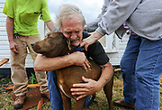 Photo by Gary Cosby Jr.  A small tornado touched down in Athens and marched through Limestone County Friday, March 02, 2012.  Greg Cook hugs his dog Coco after finding her inside his destroyed home on Ennis Rd.  The dog appeared to be uninjured except for a bloody nose.