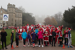Windsor, UK. 24 November, 2019. Fun runners dressed as Santa Claus and his reindeer take part in the 2019 Windsor Santa Dash on the Long Walk in front of Windsor Castle in aid of the Alexander Devine children's hospice.
