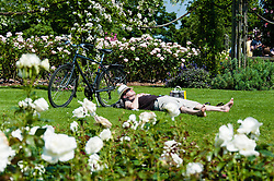 © Licensed to London News Pictures. 06/07/2013. London, UK.  A man sleeps in the sun next to his bicycle Londoners in Regents Park, central london, during a sunny saturday.  Photo credit : Richard Isaac/LNP