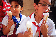 MARCH 19, 2001 - HAVANA, CUBA:  Elementary school students eat ice cream cones after school in the historic section of Havana, Cuba, March 19, 2001. Despite problems in its economy,  Cuba's educational system remains strong and is considered a role model for many developing countries. Cuba has virtually eliminated illiteracy.      .PHOTO BY JACK KURTZ/THE IMAGE WORKS PHOTO BY JACK KURTZ       WOMEN   EDUCATION  FAMILY  CHILDREN  FOOD