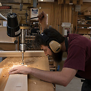 Tibout Lenfant of C.B. Fisk, inc., Gloucester, MA works on parts for a pipe organ., cutting wood precisely with a drill press.