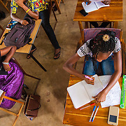 LÉGENDE: BTS génie civil 1ère année mécanique. Pendant la correction du devoir surveillé de mécanique et remises des copies aux étudiants. LIEU: CERFER, Lomé, Togo. PERSONNE(S): Plang plongé d'une étudiante qui en train de faire son devoir.