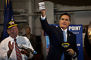 Republican presidential candidate Mitt Romney hold a gift mug and hat after addressing a group of veterans during a visit to the aircraft carrier USS Yorktown museum on October 6, 2011 in Charleston, South Carolina.