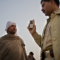 Sub-inspector, Sumer Singh (right) interviews a resident about Ramsahay Prajapati in Pilukhera village, 40km from Rantambore National Park. Information gathered by Dharmendra Khandal of Tiger Watch suggested that Prajapati supplied guns to poachers. Prajapati had fled the scene before police could arrest him however a gun and gun-making tools were discovered hidden in his workshop and home. Prajapati's wife and neighbours were advised to present him to the police on his return home. ..Sariska National Park in Rajasthan was once home to dozens of tigers but by 2005 poaching had resulted in their complete eradication. Recognising the urgent need for intervention, the Indian and Rajasthan-state governments began the reintroduction of tigers into Sariska. Two cats were airlifted 200 km from Ranthambore National Park in June 2008. On November 5th an attempt to relocate a third tiger was postponed until later in the month. This relocation strategy is certainly an important part of the tiger conservation effort but many, including those like Dharmendra Khandal of the NGO Tiger Watch, argue that it will never be entirely successful without properly confronting the three essential issues that threaten tiger populations: poaching, habitat loss and the hunting of prey-base animals. In turn, these three issues cannot be addressed without acknowledging the malign influence of caste, poverty and poor administrative accountability. Poaching is almost exclusively undertaken by extremely poor and marginalised groups, including the Mogia caste who, without education, land and access to credit have limited alternative means of income. Many in the Mogia community also hunt bush meat for both their own consumption and to sell to others. This results in a depletion of the prey-base upon which tigers feed. Encroachment and grazing by those including the Gujar people who raise dairy herds, have led to habitat loss in Sariska and other parks. To properly tackle the problem of hunting and en