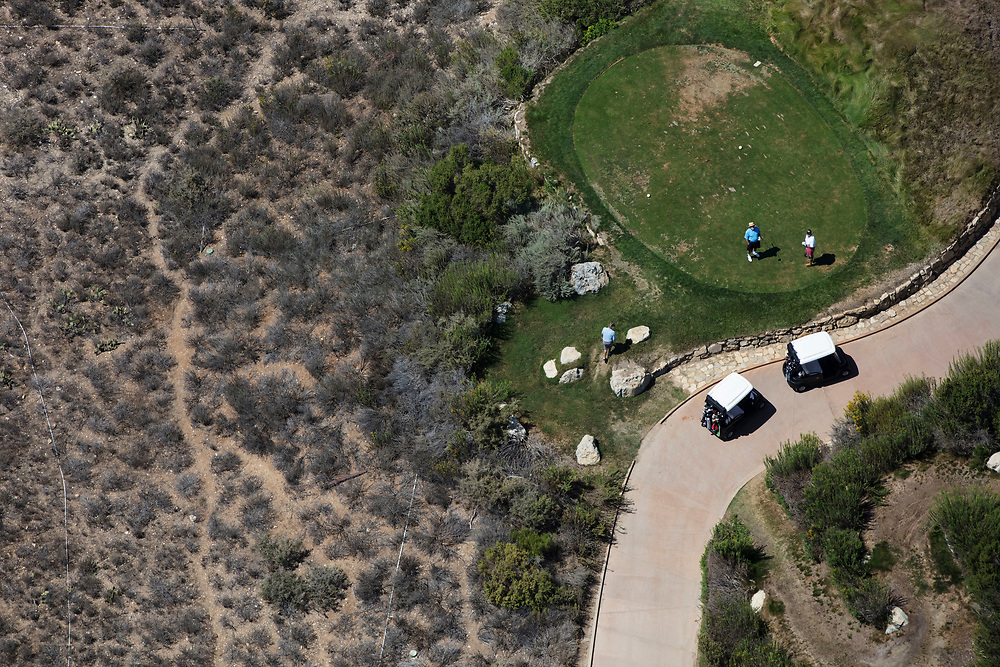 People golf on the greens of Trump National Golf Club, Los Angeles in this aerial photograph taken during the historic drought over Rancho Palos Verdes, California, U.S., on Monday, August 31, 2015. Owned by The Trump Organization, the course was formerly known as Ocean Trails Golf Club, an 18-hole course designed by Pete Dye, which was about to open when a landslide occurred. Donald Trump bought the property known for it's views of the Pacific Ocean in 2002. © 2015 Patrick T. Fallon