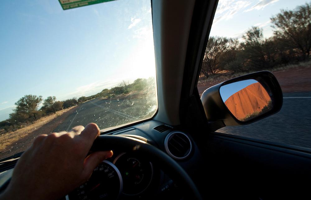 Australia, Northern Territory, Uluru - Kata Tjuta National Park, View of Ayers Rock in car's rear view mirror at sunset