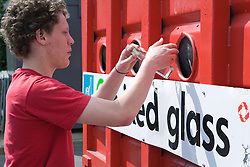 Teenaged boy recycling glass at bottle bank at city tip,