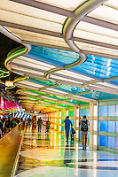 Travelers in tunnel at United terminal passing Sky's the Limit (neon sculpture by artist Michael Hayden) at O'Hare International Airport, Chicago, Illinois USA.