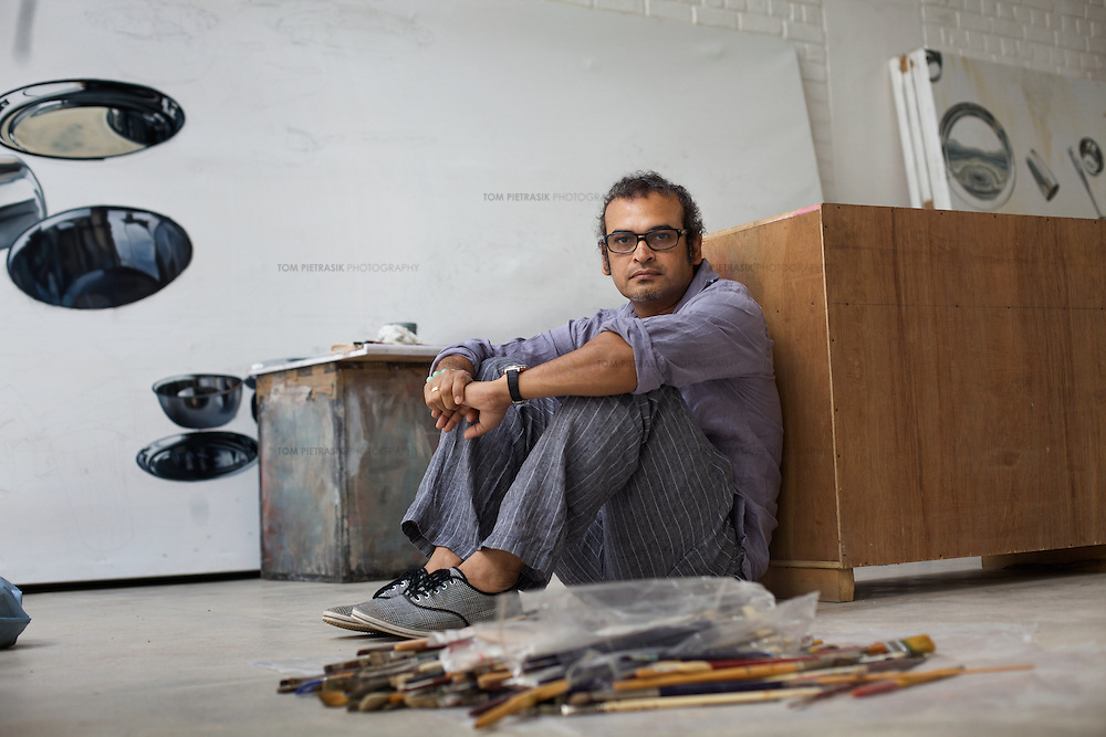 """Subodh Gupta, contemporary artist with works-in-progress in his recently completed studio in Gurgaon, a satellite town of Delhi...Gupta's most celebrated sculptures are constructed from common domestic items including the steel pots and pans that are a feature every Indian home. Of the kitchen-ware that forms the basis of his work, Gupta says,..""""The poor, the middle class and the rich use it at home. In this country, how many people have the utensils but they starve because there is no food?""""..Gupta was brought up, one of six children, to a railway-worker father in a north Indian village. ..Gupta's work fetches such huge sums of money. Two versions of his Mind Shut Down, modeled on the human skull and constructed entirely of steel kitchen utensils recently sold for EUR1 million each...Photo: Tom Pietrasik.Gurgaon, Haryana. India. .June 26th 2009"""